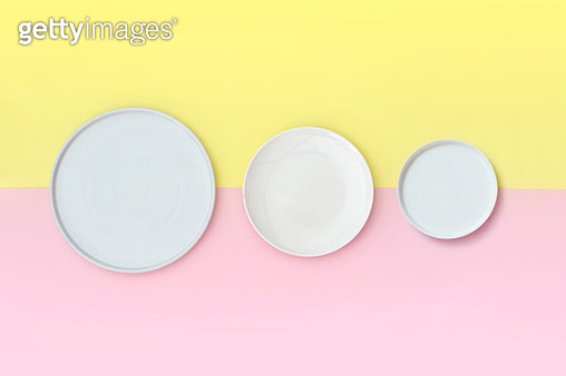 Various size of empty white plates on yellow and pink background. - gettyimageskorea