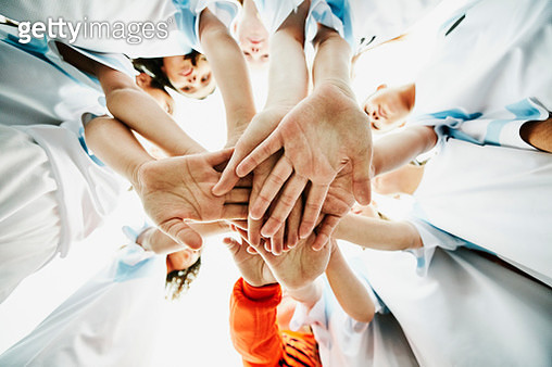 View from below of young female soccer players bringing hands together before game - gettyimageskorea