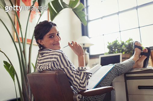 Portrait confident businesswoman working, reviewing paperwork with feet up on desk - gettyimageskorea