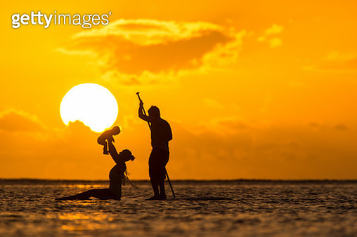 Young And Beautiful Parents Ride By Surfboard With Baby In The Indian Ocean Island Of Mauritius - gettyimageskorea