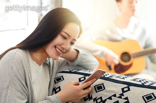 Young women see a mobile phone - gettyimageskorea