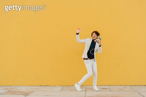 Businessman singing and dancing in front of yellow wall listening music with headphones and smartphone - gettyimageskorea