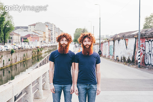 Portrait of young male hipster twins with red hair and beards standing on bridge - gettyimageskorea