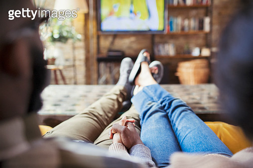 Affectionate couple holding hands, watching TV in living room - gettyimageskorea