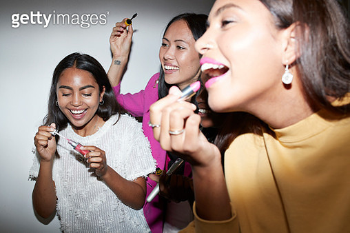 Cheerful friends doing make-up while enjoying in party at home - gettyimageskorea