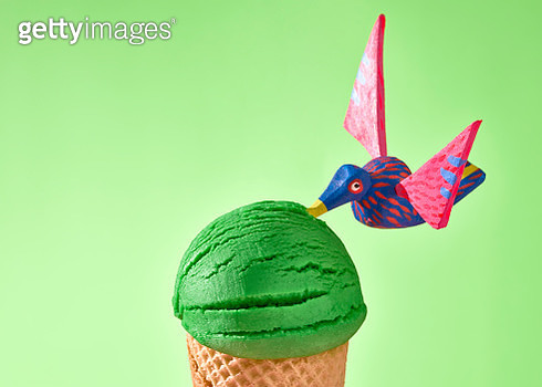 A green ice cream closeup decorated with Mexican handcrafts over a green background. - gettyimageskorea