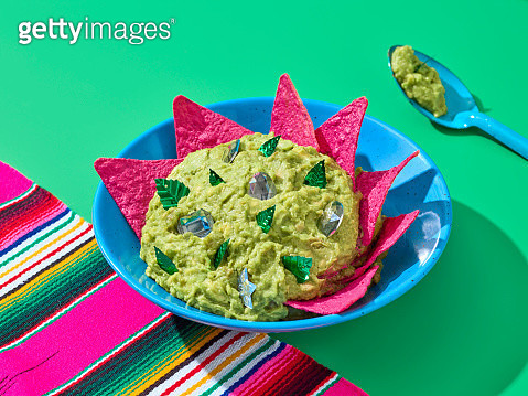 A guacamole pewter bowl with pink nachos. Shot over a green background and a sarape. - gettyimageskorea