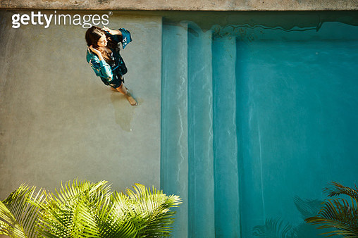 Overhead view of woman in robe standing on top step of hotel pool - gettyimageskorea