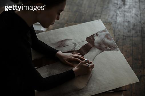 Portrait of young focused Caucasian woman sketching in art studio. - gettyimageskorea