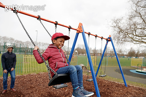 Father and son playing on the swings in the park - gettyimageskorea