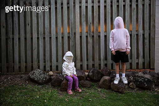 Two girls in garden wearing hoodies backwards - gettyimageskorea