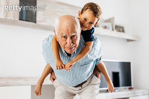 Portrait of grandfather giving his grandson a piggyback ride in the living room - gettyimageskorea