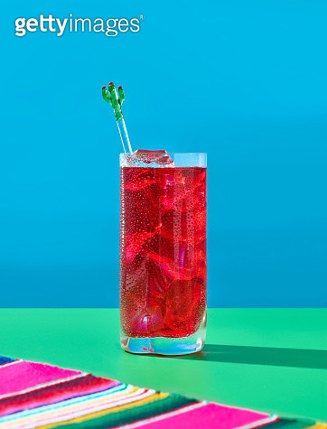 Red drink with ice over a blue background and a green table - gettyimageskorea