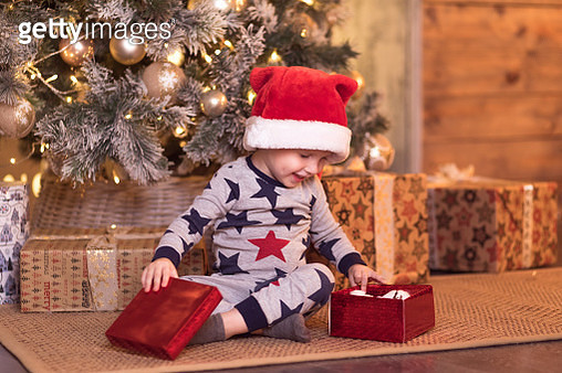 Smiling happy cute child in Santa red hat holding Christmas gift in hand near a Christmas tree - gettyimageskorea