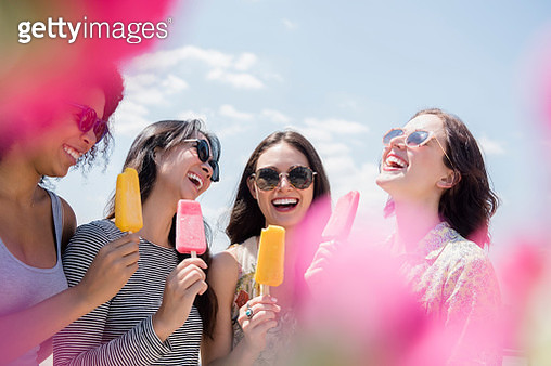 Laughing women eating flavored ice outdoors - gettyimageskorea