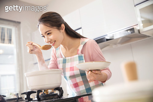Young woman soup in the kitchen - gettyimageskorea