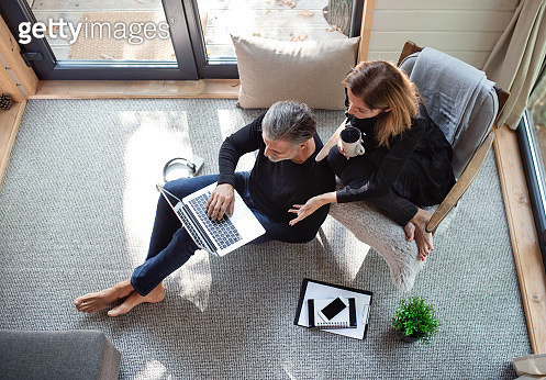 A man and woman sitting in a room in house in nature. - gettyimageskorea