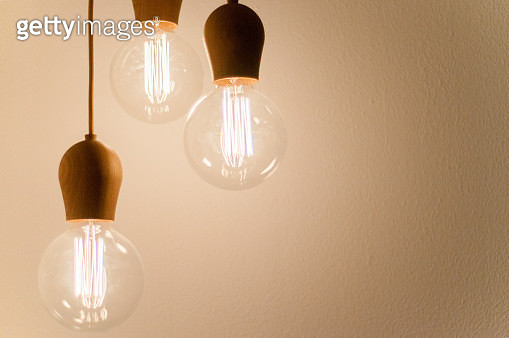 Three lit-up lightbulbs hanging by cords on a beige background. - gettyimageskorea