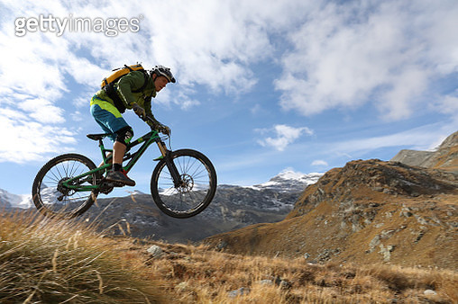 Mountain biker descends alpine slope, mountains behind - gettyimageskorea