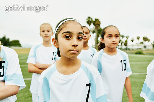 Portrait of serious young female soccer player standing on field with teammates - gettyimageskorea