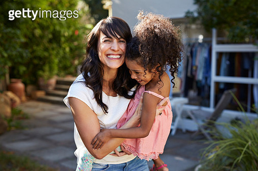Mother carrying daughter & both laughing in garden - gettyimageskorea