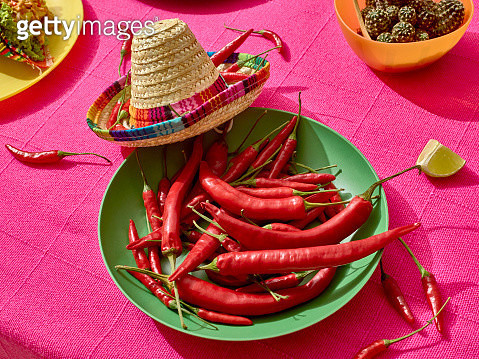 Mexican feast. A plate with red chili peppers and a Mexican hat. - gettyimageskorea