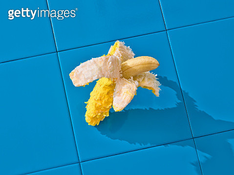 A banana shaped piñata over a blue tile floor. - gettyimageskorea
