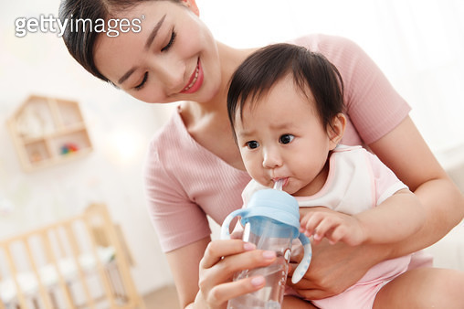Mother feeding the baby to drink - gettyimageskorea