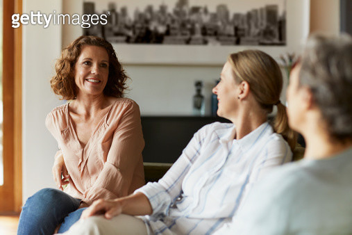 Woman conversing with friends at home - gettyimageskorea