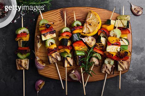 Colorful grilled summer seasonal vegetables skewers on rustic wooden board viewed from above - gettyimageskorea
