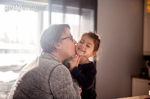 Grandmother give a kiss to her 3 years old granddaughter. The woman give a kiss to her sweet little granddaughter. She is sit on the kitchen counter. Photo was taken in Quebec Canada. - gettyimageskorea
