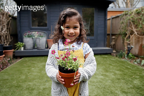Toddler with wavy hair holding potted plant in garden - gettyimageskorea