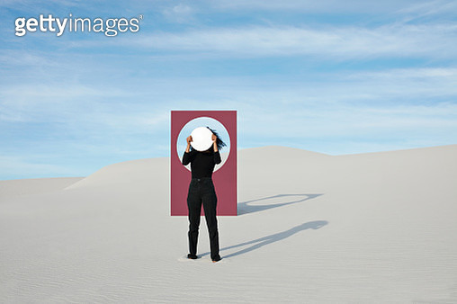 Young woman holding mirror while standing against portal at desert - gettyimageskorea