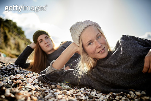 Portrait of two smiling female friends lying on shore - gettyimageskorea