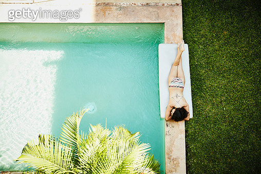 Overhead view of woman lying next to pool in courtyard of outdoor spa - gettyimageskorea