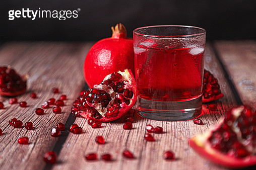 Juice of pomegranate in glass. Half pomegranate and ripe pomegranate fruit with seeds on rustic wood background. - gettyimageskorea