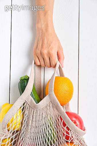 Fresh juicy fruits and vegetables, in a reusable shopping bag. A girl or woman holds a string bag made from recycled materials on a white wooden table or background. Vegetarianism, Veganism. No plastic. - gettyimageskorea
