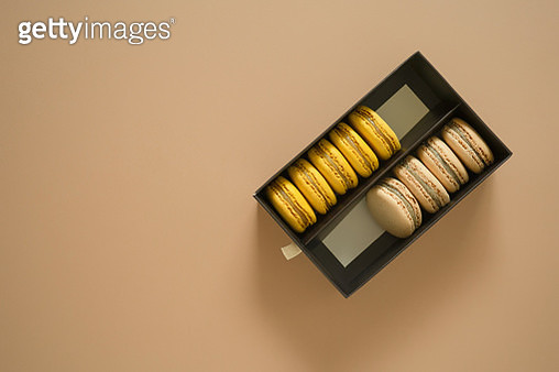 High Angle View Of Macaroons In Box On Brown Background - gettyimageskorea