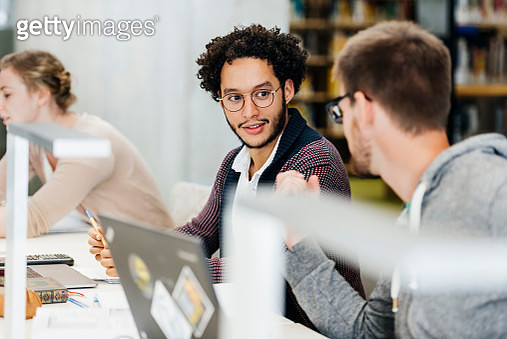 Two Students Talking To Each Other While Studying In Library - gettyimageskorea