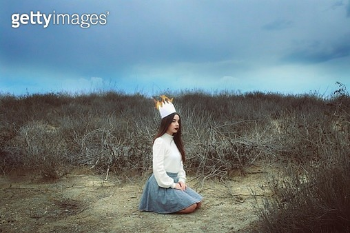 Woman Sitting On Field Against Sky - gettyimageskorea