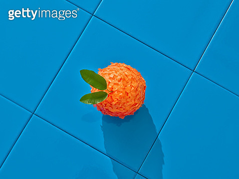 An orange shaped piñata over a blue tile floor. - gettyimageskorea