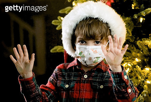 Lonely Serious pensive Little boy wearing a Santa hat and a protective face mask looking Through a window at night - gettyimageskorea