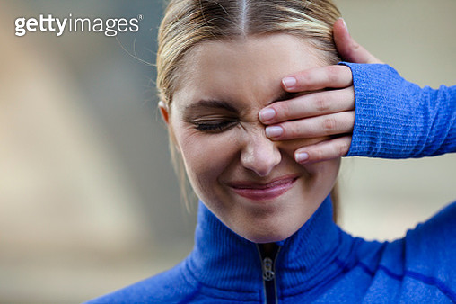Young woman squinting at discomfort in eye - gettyimageskorea