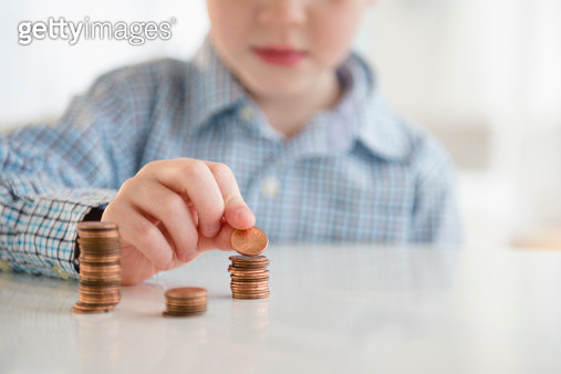 USA, New Jersey, Jersey City, Boy (4-5) stacking coins - gettyimageskorea