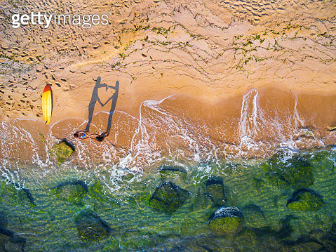 Aerial view of a couple having fun on a beach and making heart with hands - gettyimageskorea
