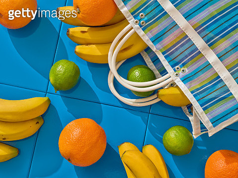 Lemons, oranges and bananas over a blue tile floor, out of a market bag - gettyimageskorea