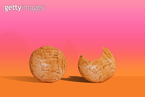 A pair of home-made peanut butter cookies on an orange table against a gradient background with strong shadows. One cookie has a missing bite. - gettyimageskorea