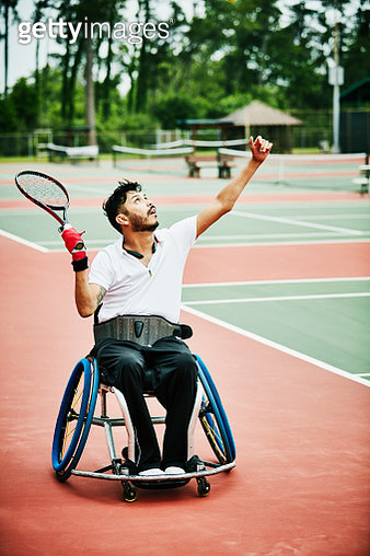 Adaptive athlete serving while playing wheelchair tennis - gettyimageskorea