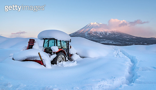 snow covered Tractor in front of Yōtei-zan volcano - gettyimageskorea