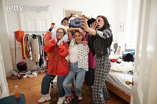 Cheerful young female friends gesturing while taking selfie in bedroom at home - gettyimageskorea